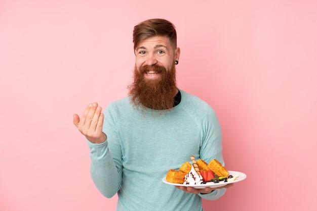 手で来ることを招待して孤立したピンクの壁にワッフルを保持している長いひげを持つ赤毛の男。あなたが来て幸せ