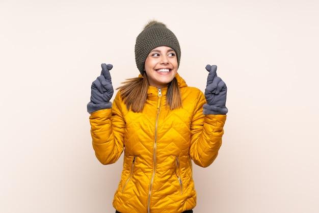 指を交差で壁を越えて冬の帽子を持つ女性