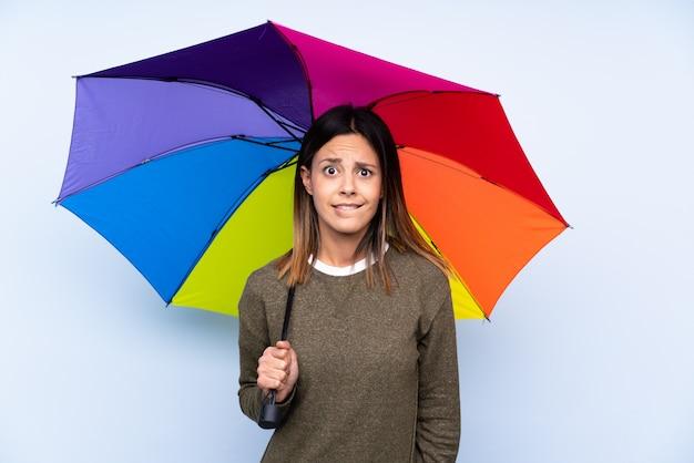 疑問を持つと混乱の表情で青い壁に傘を保持している若いブルネットの女性