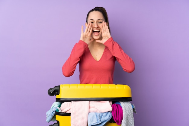 Путешественник женщина с чемоданом, полным одежды над изолированных фиолетовый стена кричит с широко открытым ртом
