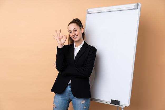 Молодая бизнес-леди над изолированной стеной давая представление на белой доске и показывая одобренный знак с пальцами