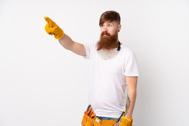 透明な画面に触れる分離の白い壁に長いひげを持つ赤毛の電気技師男