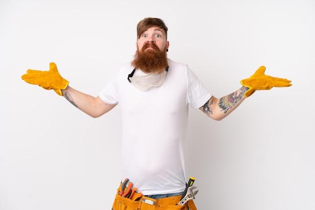 混乱した表情で疑問を持つ孤立した白い壁の上の長いひげを持つ赤毛電気技師男