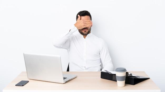 Молодой предприниматель в рабочем месте, охватывающих глаза руками. не хочу что-то видеть