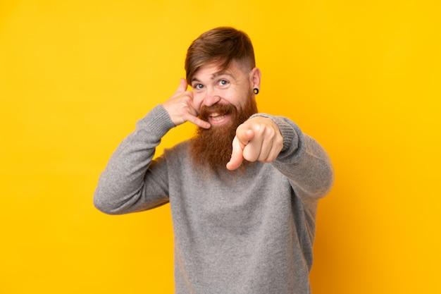 Рыжий мужчина с длинной бородой над изолированной желтой стеной, делая жест телефона и указывая спереди