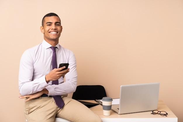 Молодой деловой человек в офисе смеется