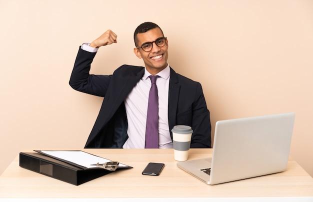 ノートパソコンと強力なジェスチャーをしている他のドキュメントと彼のオフィスで若いビジネスマン