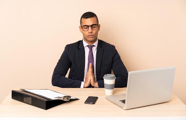 ノートパソコンと他のドキュメントと彼のオフィスで若いビジネスマンは手のひらを一緒に保ちます。人は何かを求めます