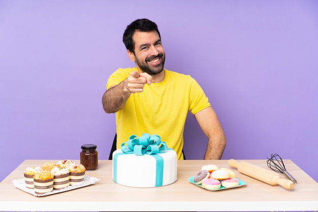 お菓子でいっぱいのテーブルを持つペストリー男