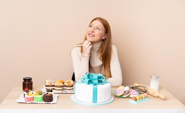 お菓子でいっぱいのテーブルを持つペストリー女性