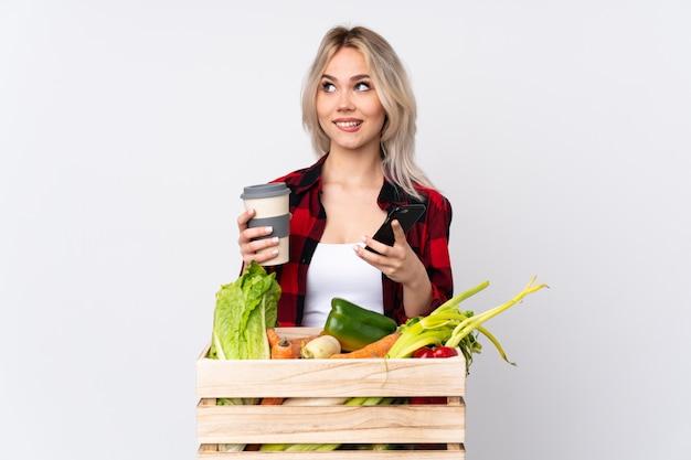 野菜の箱を持つ農家の女性