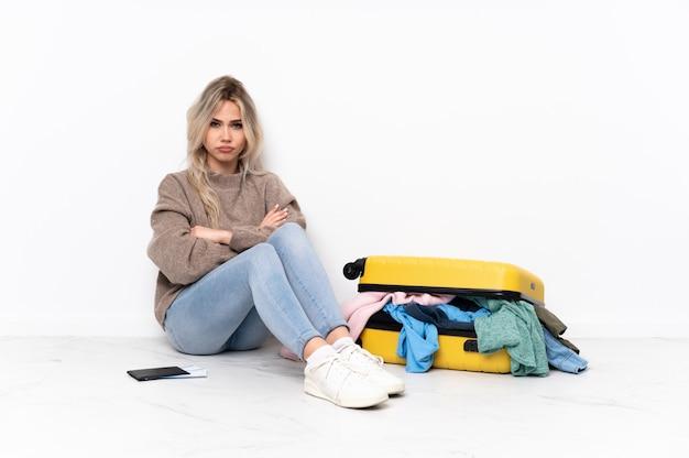 Молодая женщина сидит на полу с чемоданом