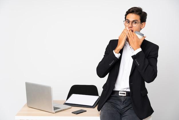 Бизнесмен в своем кабинете на белой стене с удивленным выражением лица