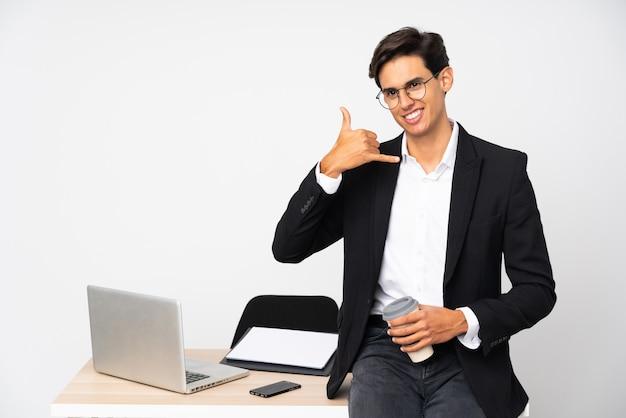 Бизнесмен в своем кабинете над белой стеной, делая жест телефона