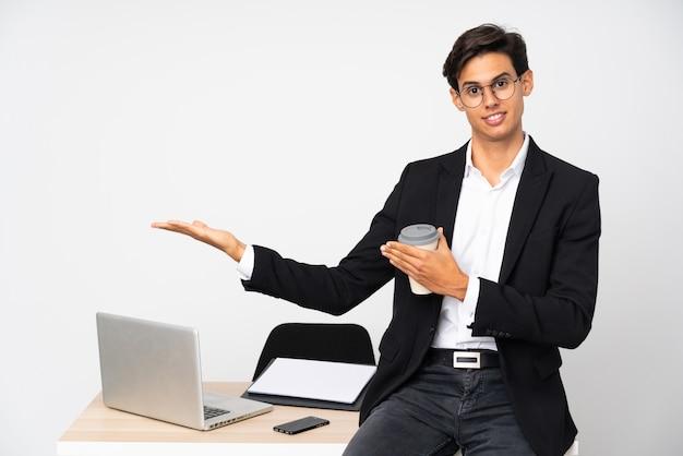 Бизнесмен в своем кабинете над белой стеной, протягивая руки в сторону за приглашение прийти
