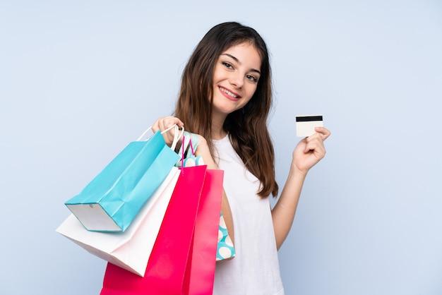 買い物袋とクレジットカードを保持している青い壁の上の若いブルネットの女性