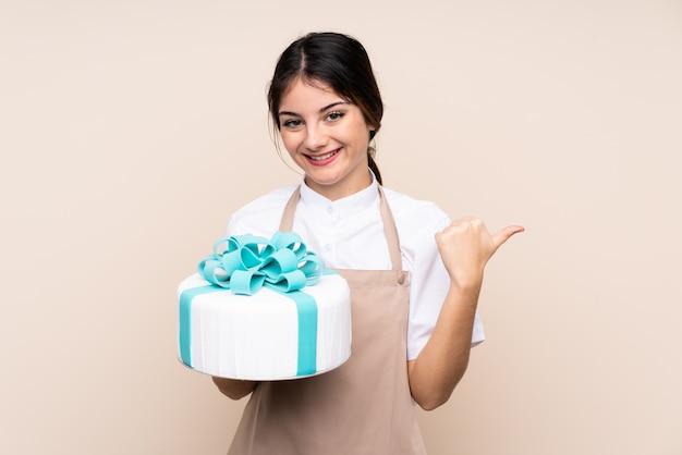製品を提示する側を指す壁に大きなケーキを保持しているパティシエの女性