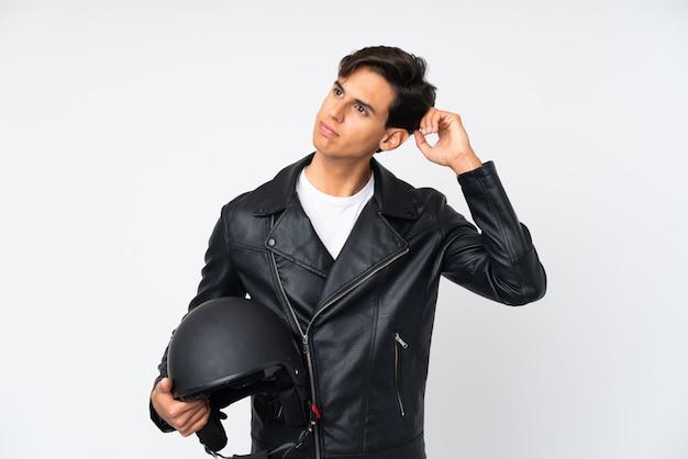 Мужчина держит мотоциклетный шлем над белой стеной с сомнением и смущенным выражением лица