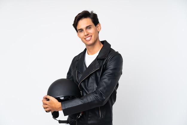 Мужчина держит мотоциклетный шлем над белой стеной, глядя в сторону
