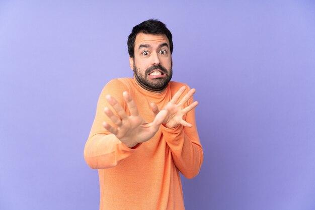 正面に手を伸ばして緊張の紫色の壁の上の白人のハンサムな男