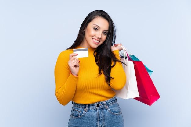 買い物袋とクレジットカードを保持している青い壁の上のコロンビアの少女