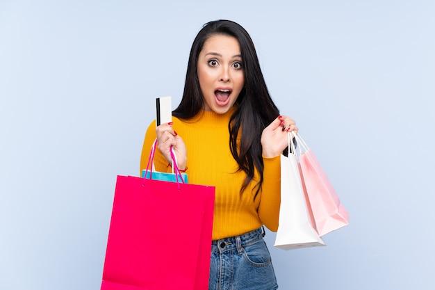 買い物袋を保持していると驚いた青い壁の上の若いコロンビアの女の子