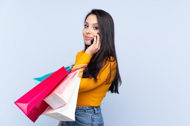 買い物袋を押し、彼女の携帯電話で友人を呼び出す青い壁の上のコロンビアの少女