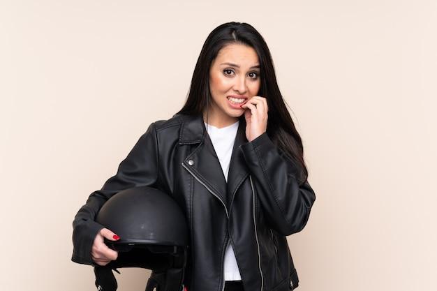 神経質で怖い壁にオートバイのヘルメットを保持しているコロンビアの少女