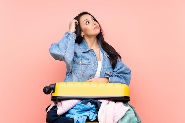 疑問を持つピンクの壁の上の服でいっぱいのスーツケースと混乱した表情を持つ旅行者コロンビアの女の子