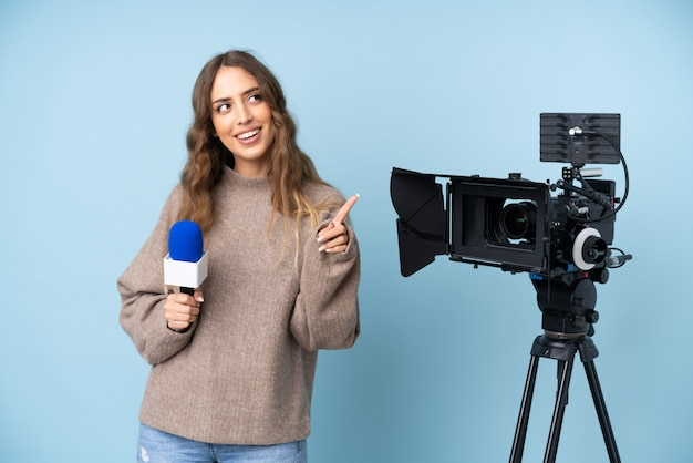 記者の若い女性はマイクを保持し、人差し指で指しているニュースを報告する素晴らしいアイデア