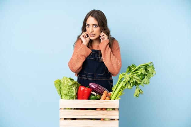 Фермер со свежесобранными овощами в расстроенной коробке и закрывающих уши