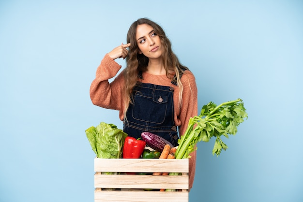 Фермер со свежесобранными овощами в коробке делает жест безумия, положив палец на голову