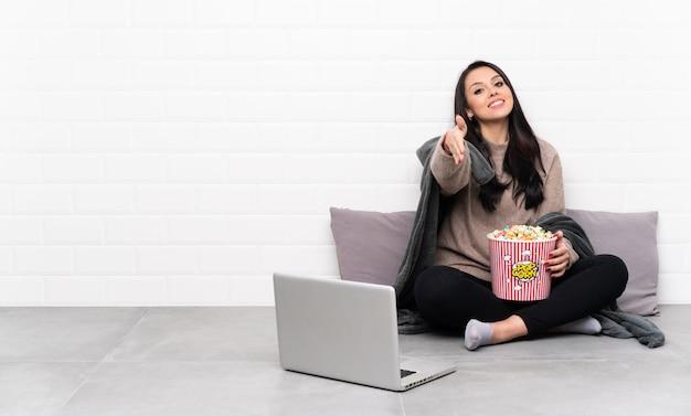 Молодая колумбийская девушка, держащая миску попкорна и показывающая фильм в ноутбуке, пожимающая руку за заключение хорошей сделки