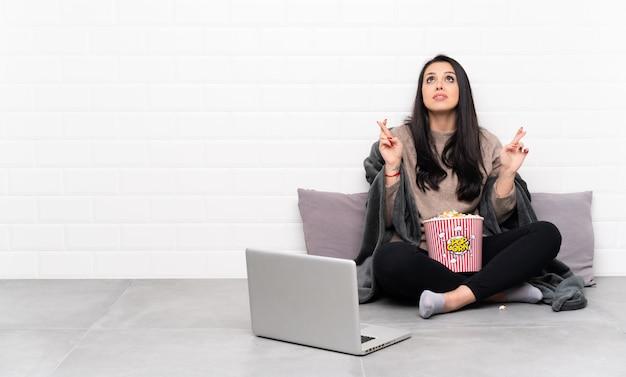 ポップコーンのボールを保持していると指を交差し、最高を願ってノートパソコンで映画を見せてコロンビア少女