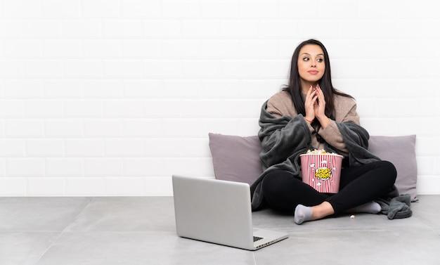 Молодая колумбийская девушка держит миску попкорна и показывает фильм в ноутбуке, замышляя что-то
