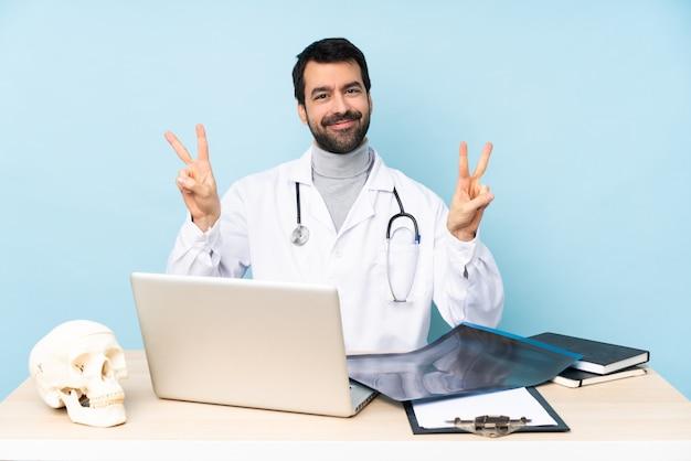 Профессиональный травматолог на рабочем месте, показывая знак победы обеими руками