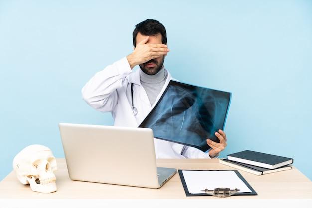 Профессиональный травматолог на рабочем месте, закрыв глаза руками. не хочу что-то видеть