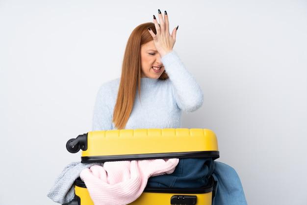 混乱した表情で疑問を持つ服でいっぱいのスーツケースを持つ旅行者女性