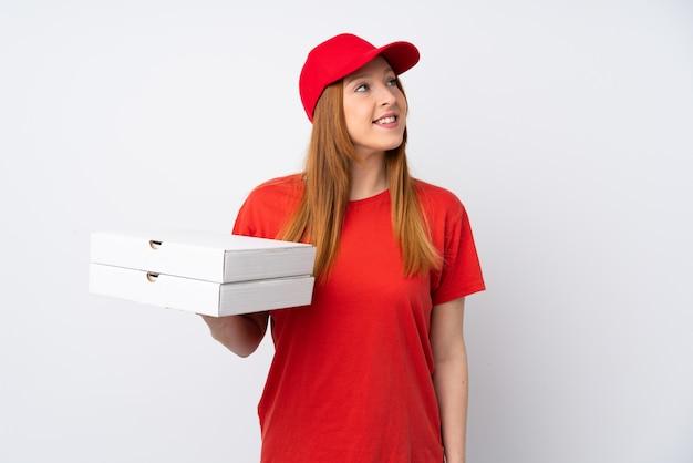 笑顔ながら見上げるピンクの壁にピザを保持しているピザ配達の女性