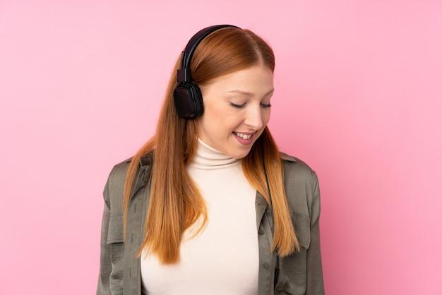 ピンクの音楽を聴く上の若い赤毛の女性