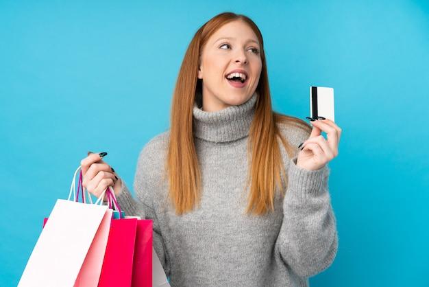 買い物袋とクレジットカードを保持している青の上の若い赤毛の女性