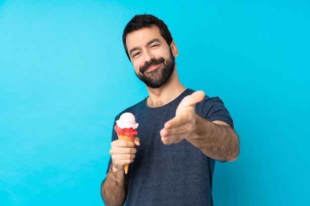 かなりを閉じるために手を振って青い上のコルネットアイスクリームと若い男