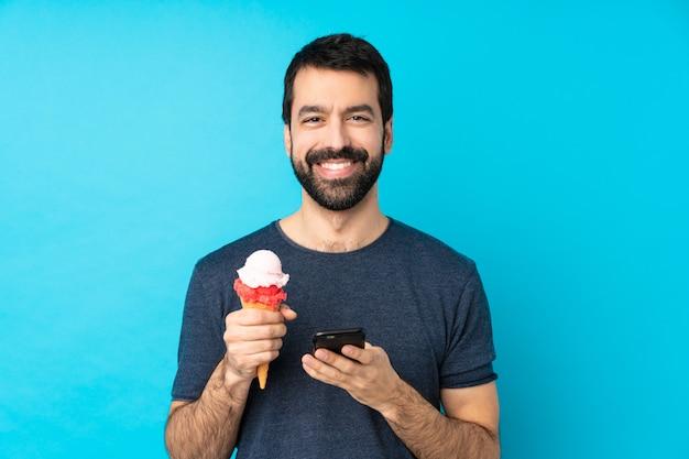 携帯電話でメッセージを送信する青い上のコルネットアイスクリームを持つ若者