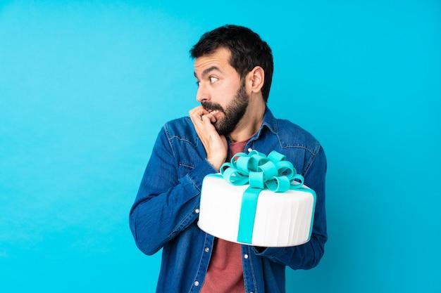 口の中に手を入れて神経質で怖い青に大きなケーキを持つ若いハンサムな男