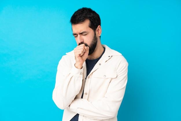 青の上に白いコーデュロイジャケットを持つ若いハンサムな男は咳と気分が悪い