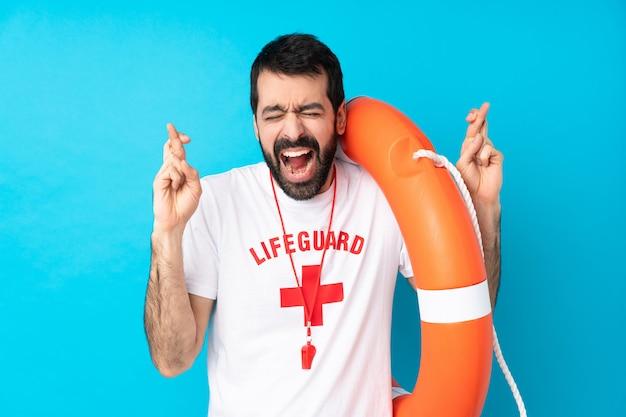 Спасатель человек над синим с скрестив пальцы