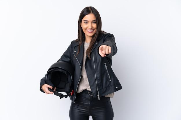 自信を持って式であなたに白いポイント指でオートバイのヘルメットを持つ若いブルネットの女性