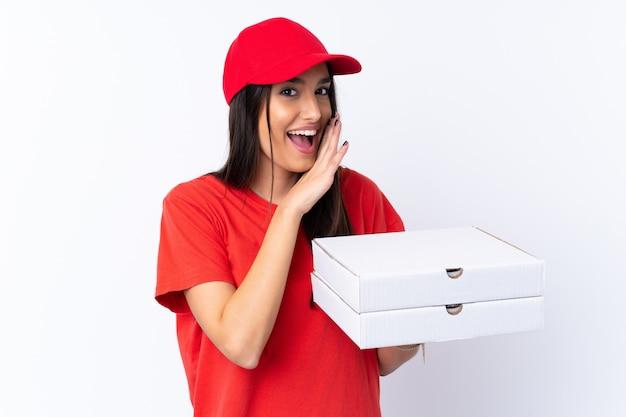 何かをささやく白い壁にピザを保持しているピザ配達の女性
