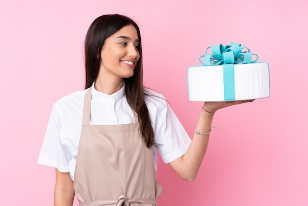幸せそうな表情で大きなケーキを持つ若い女性