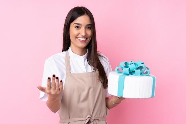手に来るように招待して大きなケーキを持つ若い女性。あなたが来て幸せ